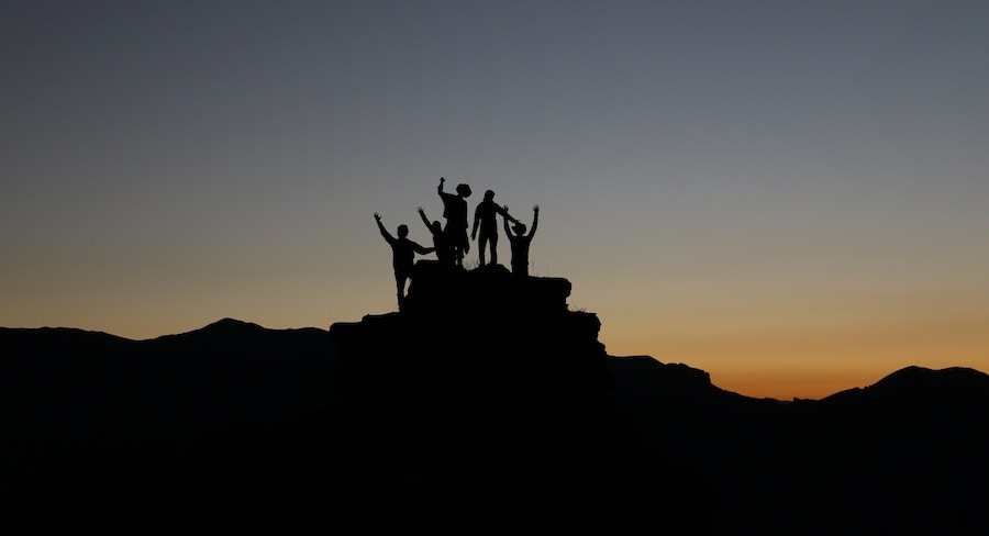 People climbing on a rock in sunset